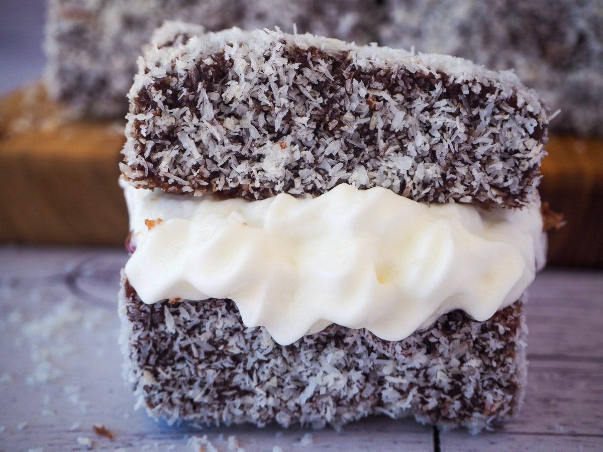 Close up lamington filled with jam and cream.