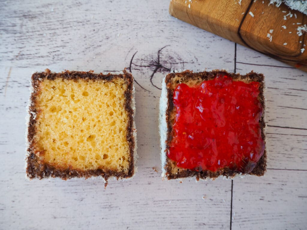 Cut open lamington with jam on one side
