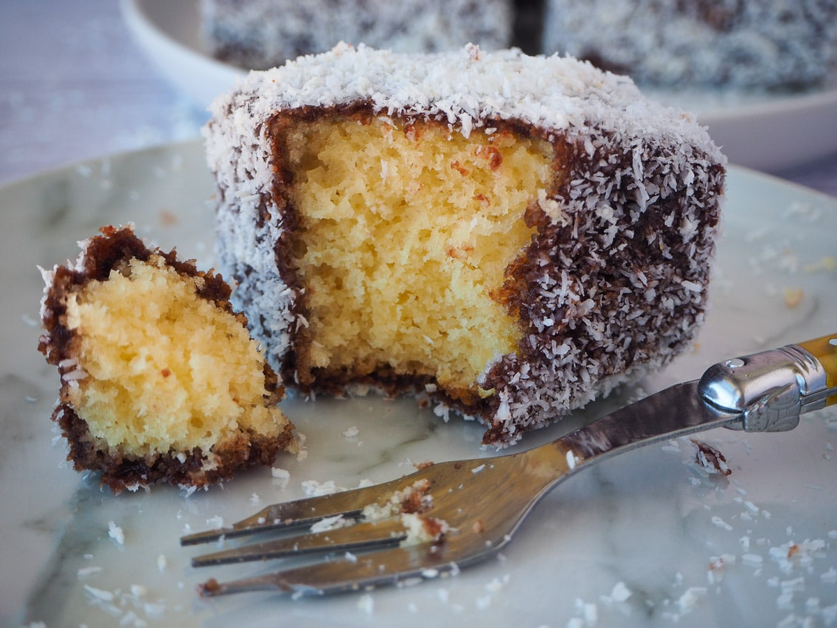 Close up of lamington with a piece taken out with a fork and vintage cake for next to it.