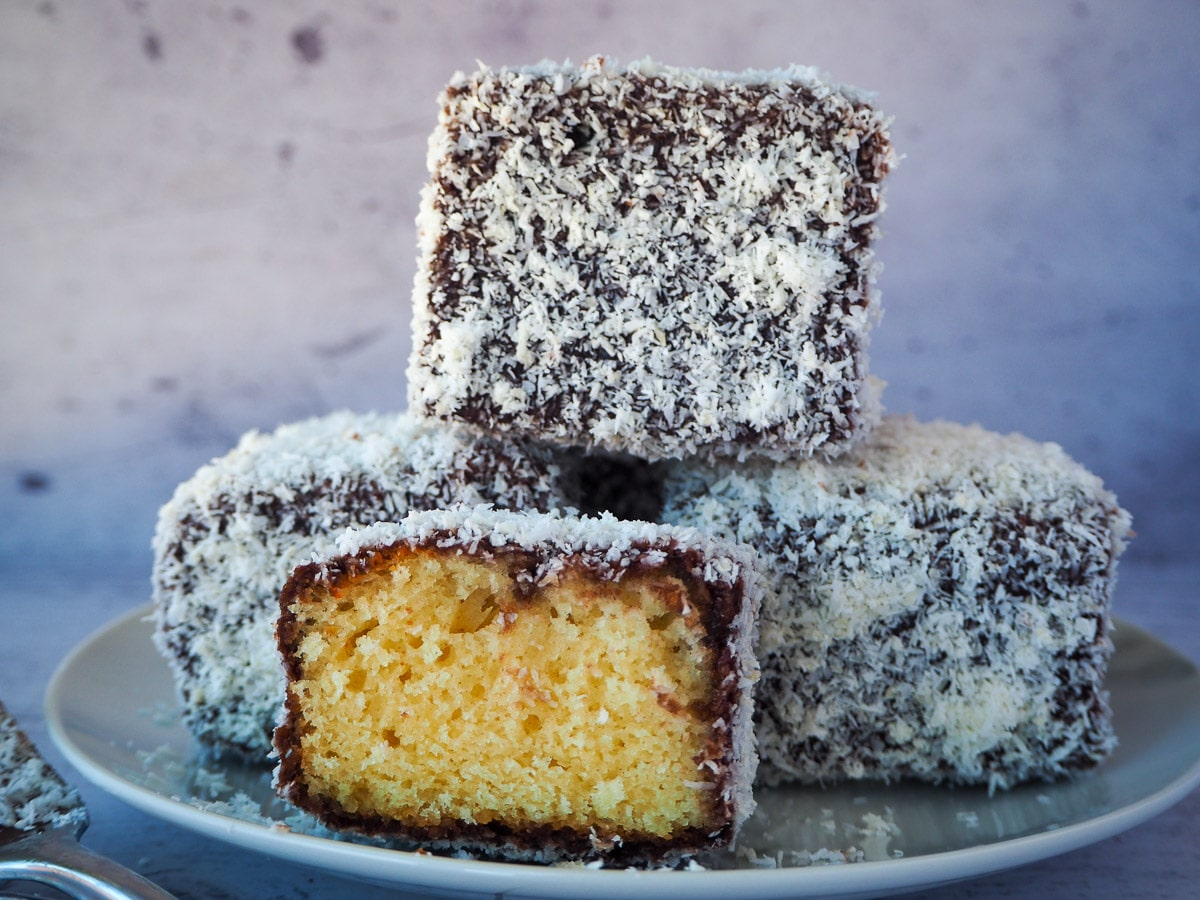 Stack of three lamingtons with a lamington cut open in front.
