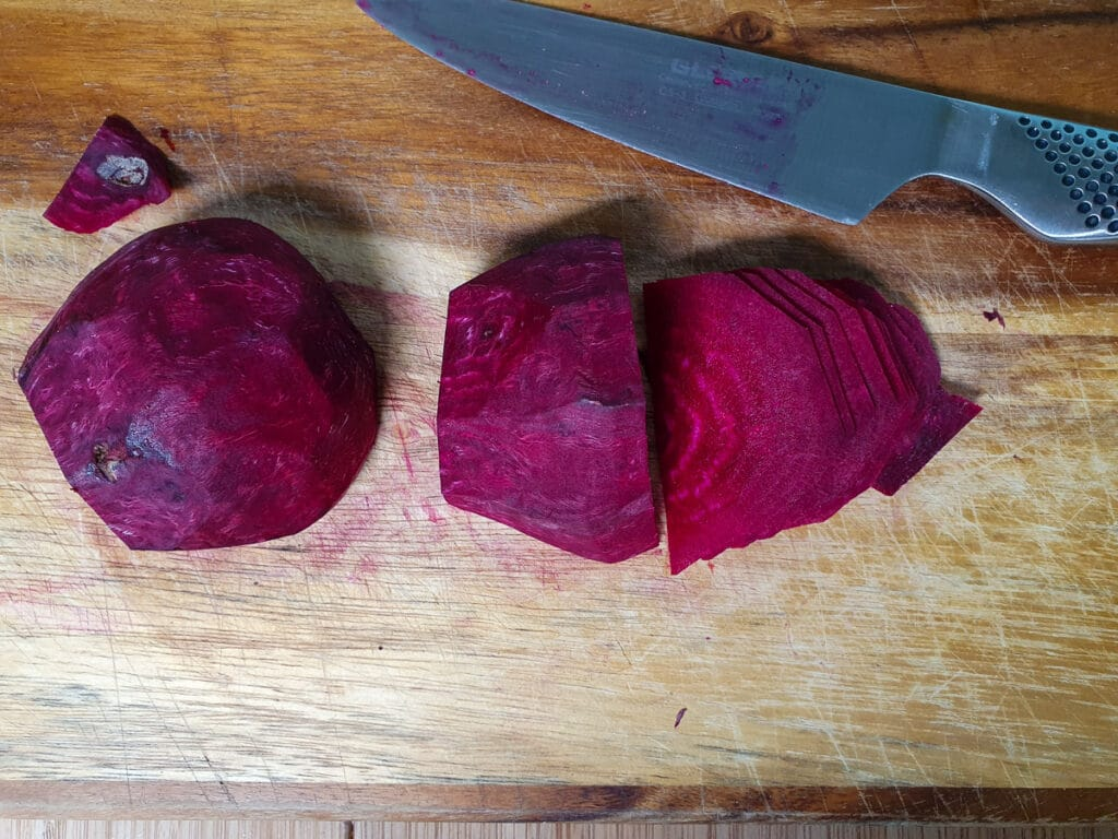 Thinly slicing peeled beets with a sharp knife.