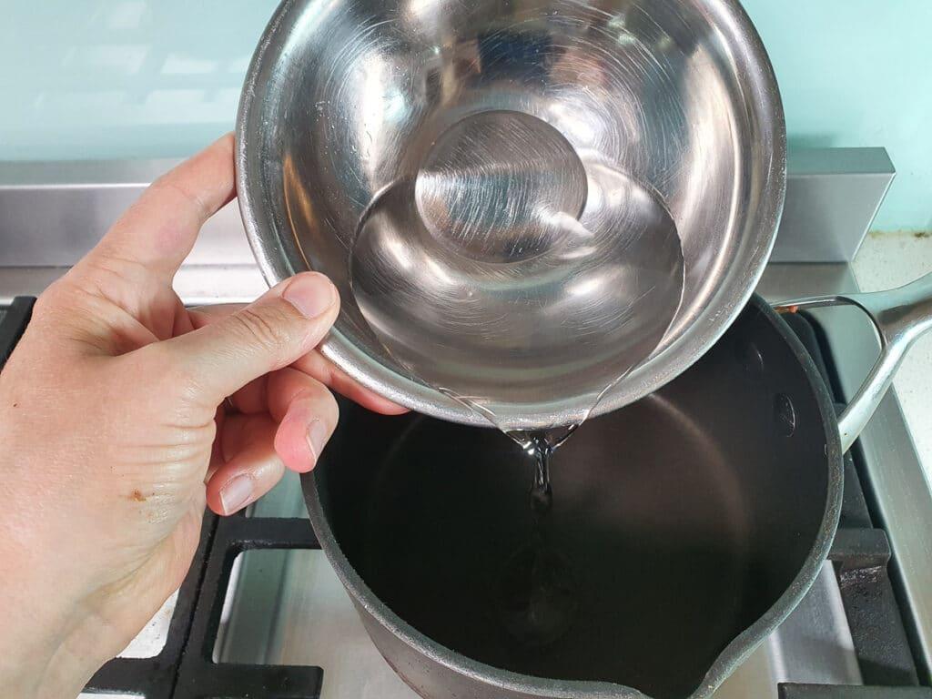 Adding vinegar to pot on stove.