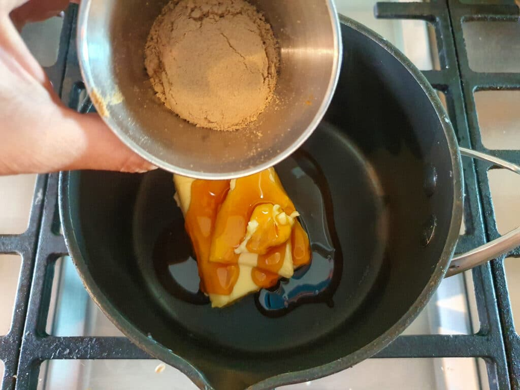 Adding ground ginger to pot on stove.