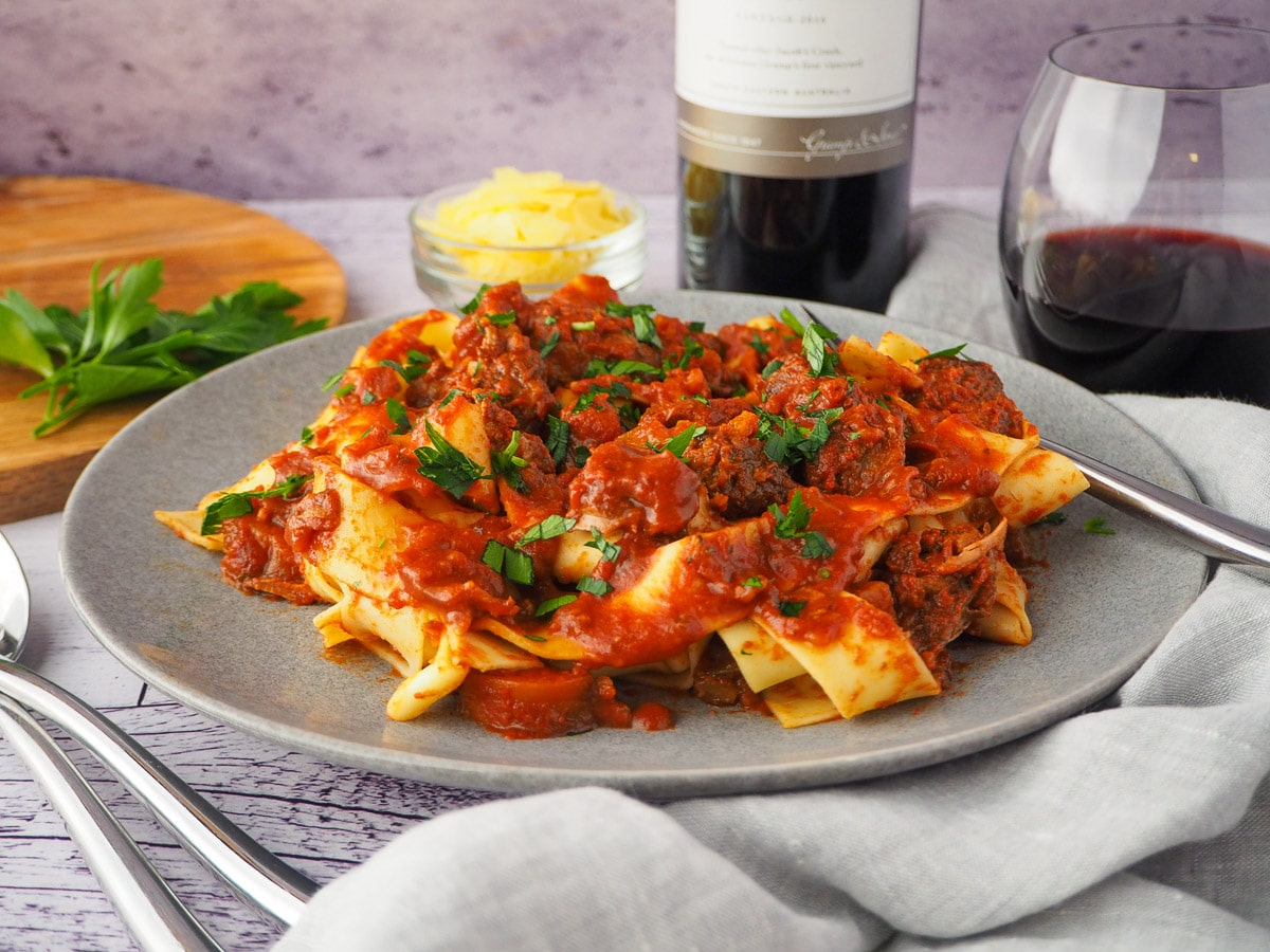Plate of slow cooker lamb ragu, garnished with chopped parsley, surrounded by serving cutlery, glass of red wine, bowl of parmesan cheese and chopping board with parsley on it.