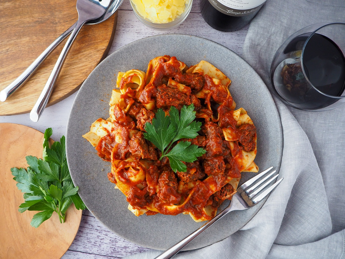 Plate of slow cooker lamb ragu, garnished with parsley, surrounded by serving cutlery, glass of red wine, bowl of parmesan cheese and chopping board with parsley on it.