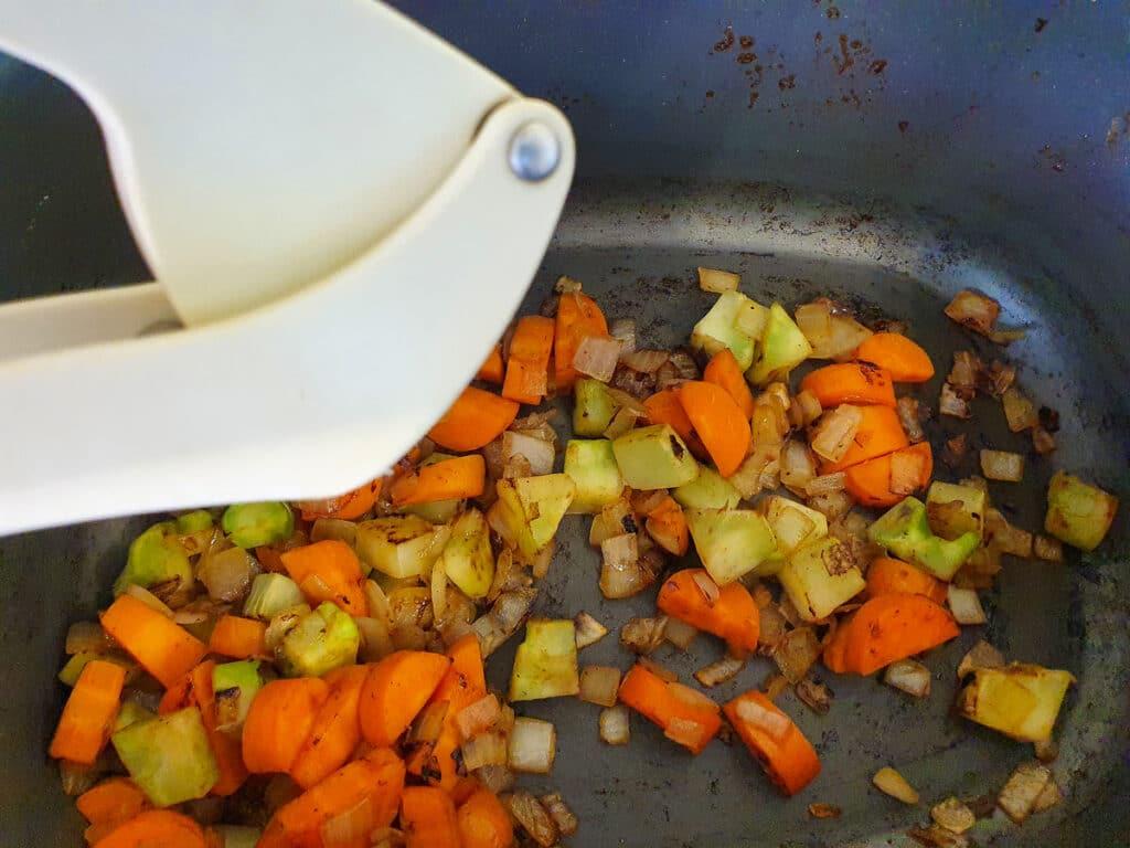 Adding crushed garlic to vegies.