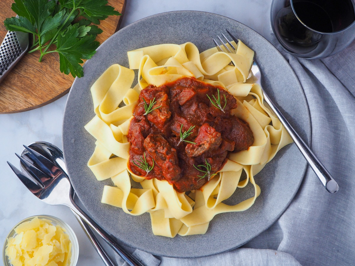 Plate of slow cooker lamb ragu, garnished with rosemary, surrounded by serving cutlery, glass of red wine, bowl of parmesan cheese and chopping board with parsley on it.