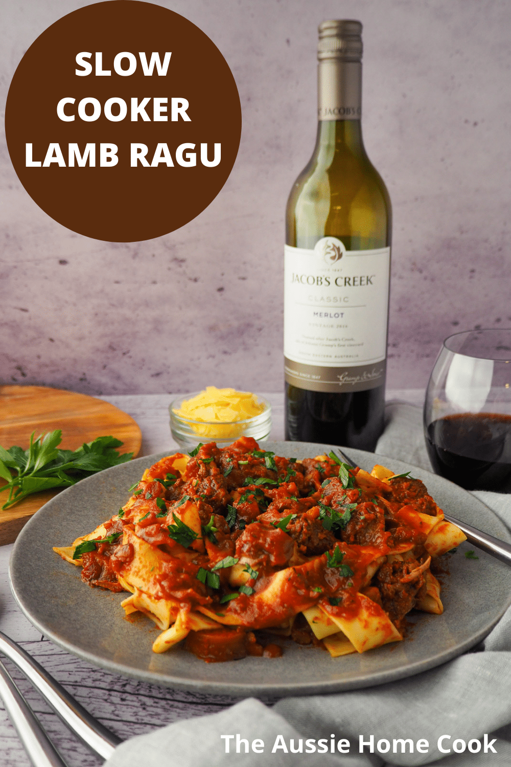 Plate of slow cooker lamb ragu, garnished with chopped parsley, surrounded by serving cutlery, glass of red wine, bowl of parmesan cheese and chopping board with parsley on it and text overlay, slow cooker lamb ragu, The Aussie Home Cook.
