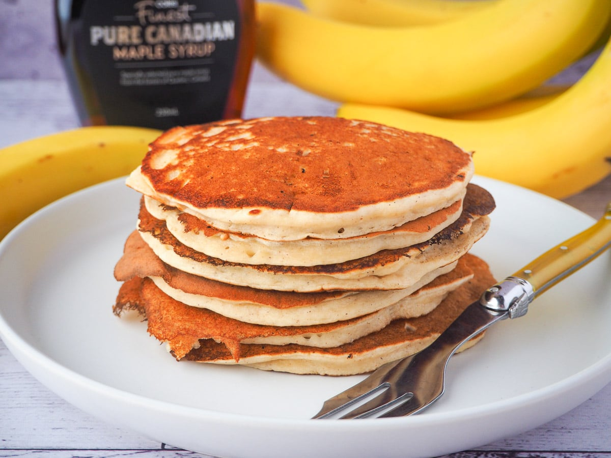 Stack of banana pikelets on a plate, with a vintage spoon on the side, surrounded by fresh whole bananas and bottle of maple syrup in the background.