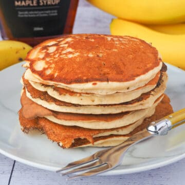 Close up stack of banana pikelets on a plate, with a vintage spoon on the side, surrounded by fresh whole bananas and bottle of maple syrup in the background.