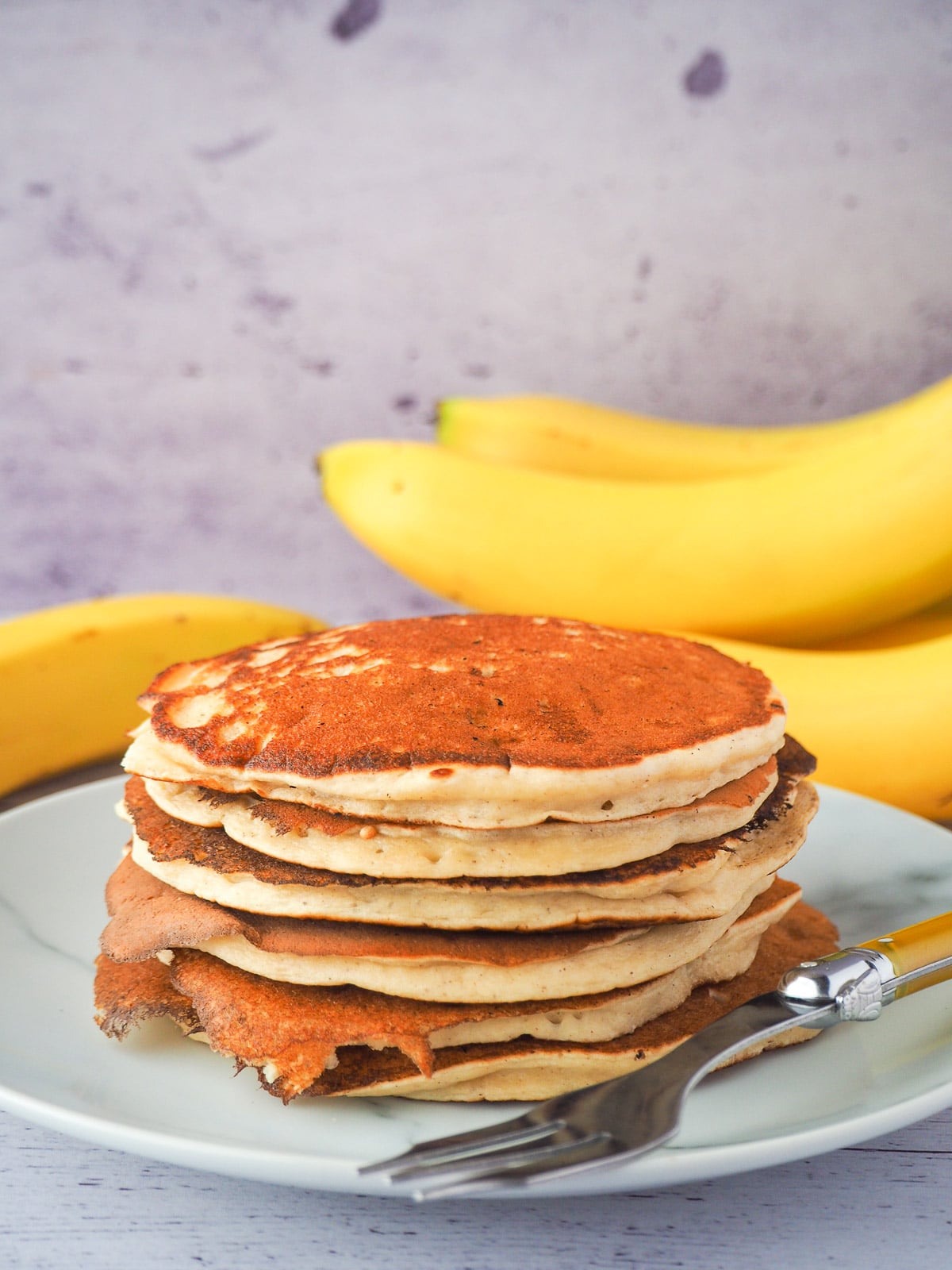 Stack of banana pikelets on a plate, with a vintage spoon on the side, surrounded by fresh whole bananas.