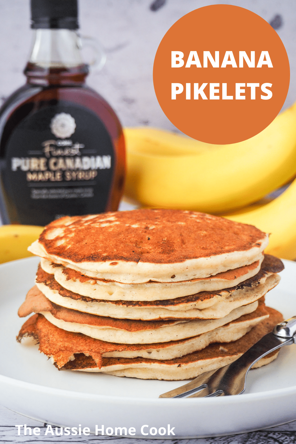 Stack of banana pikelets on a plate, with a vintage spoon on the side, surrounded by fresh whole bananas and bottle of maple syrup in the background and text overlay, banana pikelets, The Aussie Home Cook.