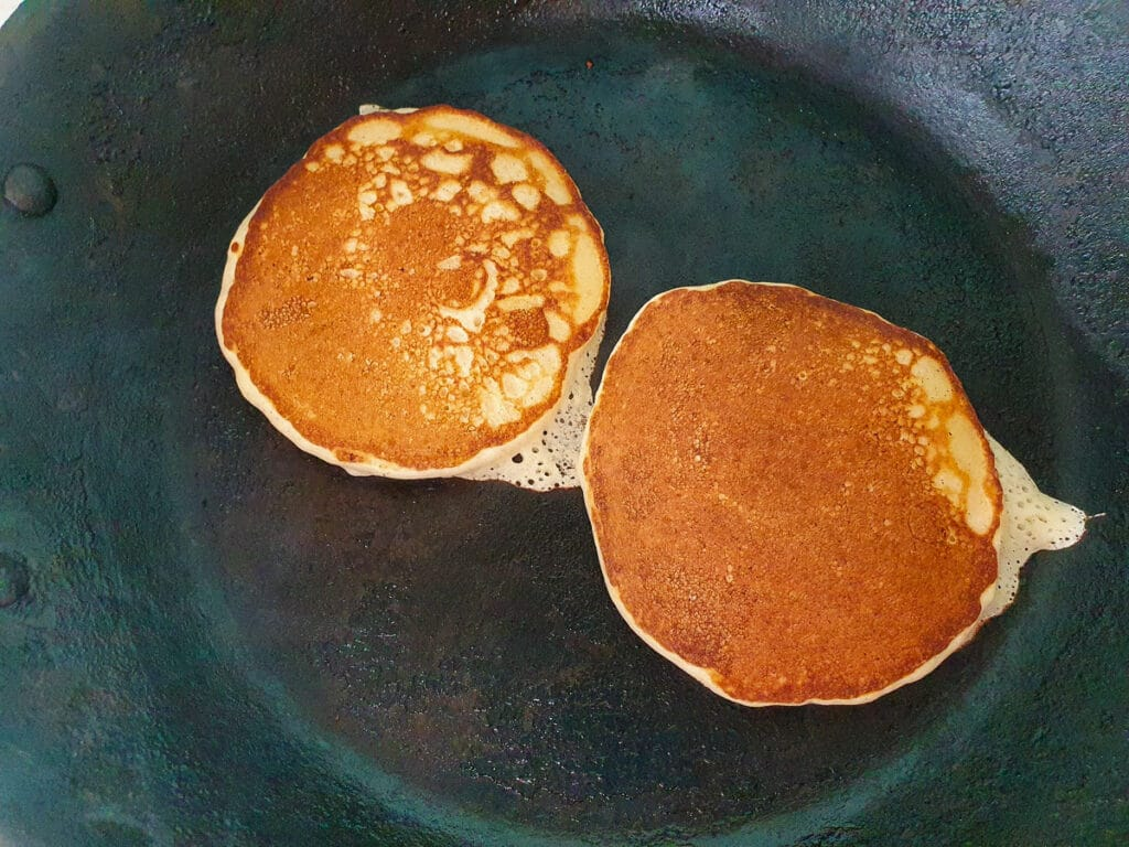 Flipped banana pikelets cooking on the other side.