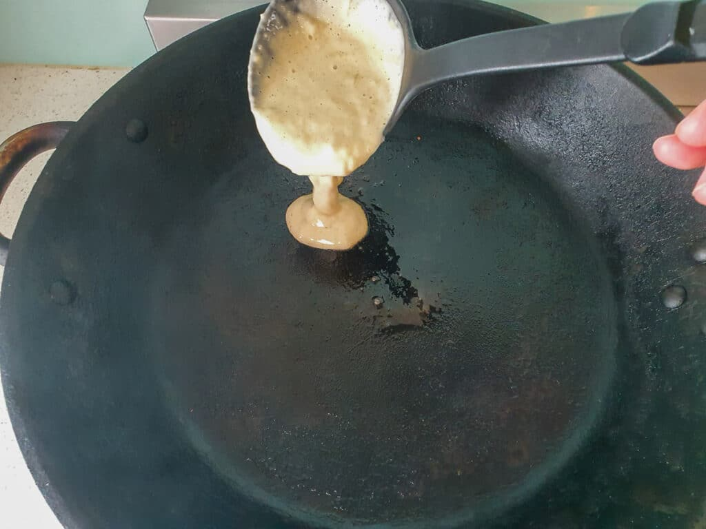 Ladling pikelet mix into hot frying pan.