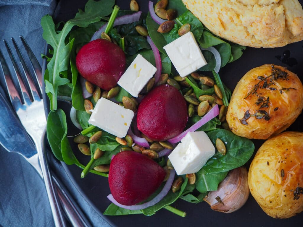 Beetroot salad on a plate, served with damper and roasted mini potatoes and cutlery on the side.