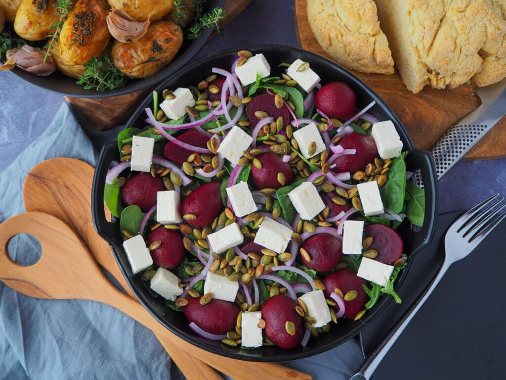 Beetroot salad on a plate, with damper and mini potatoes on the side, salad servers and a plate and fork.