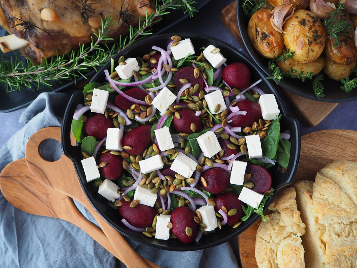 Beetroot salad on a plate, with damper and roasted mini potatoes on the side.