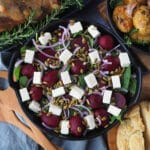 Close up beetroot salad on a plate, with damper and roasted mini potatoes on the side.