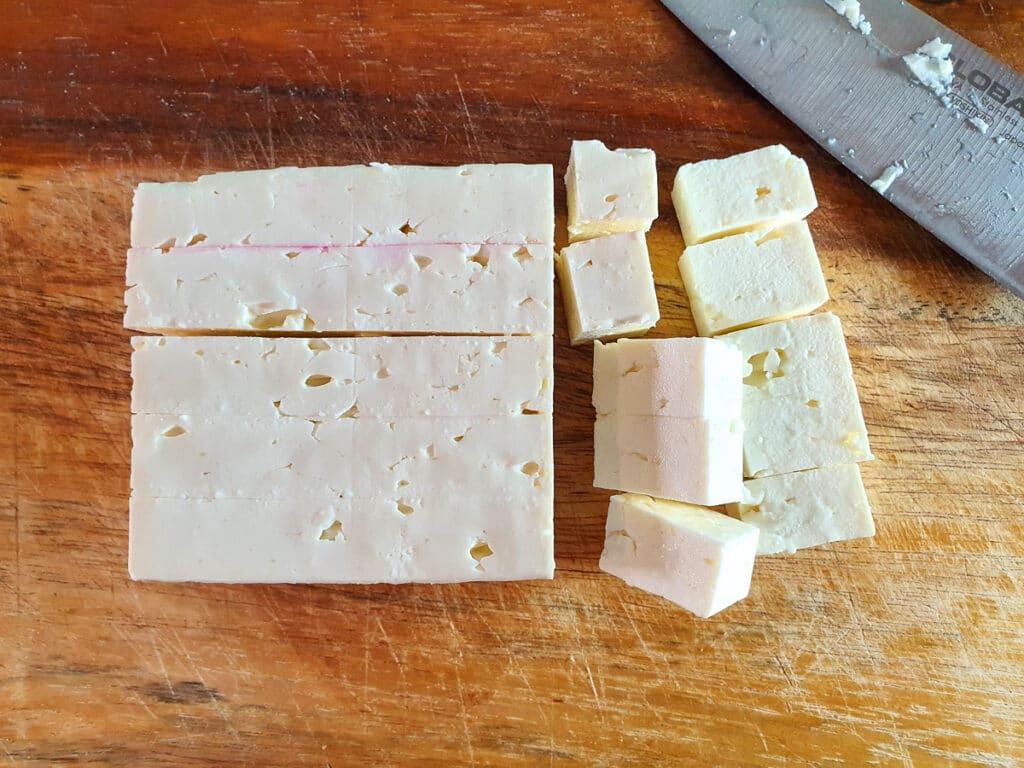 Cubing fetta cheese.