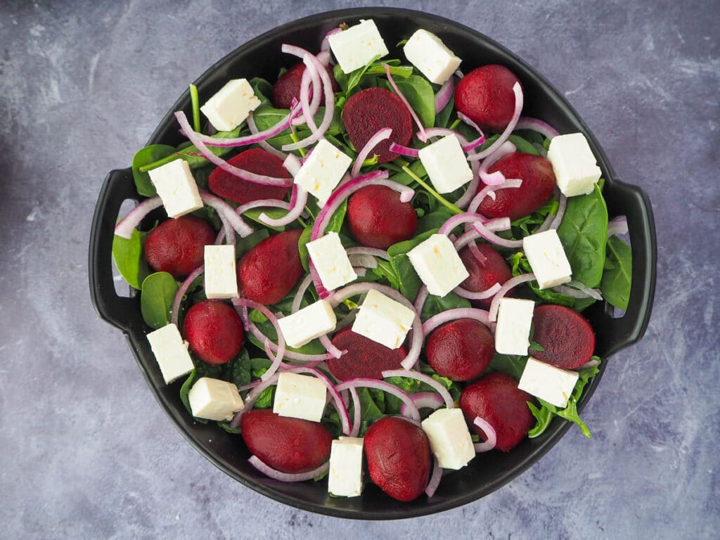Adding finely sliced cubed fetta cheese to the salad.
