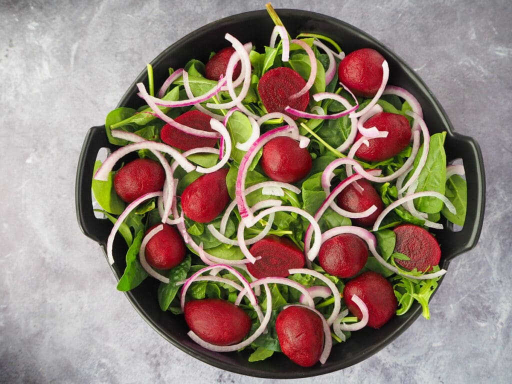 Adding finely sliced red onion to the salad.