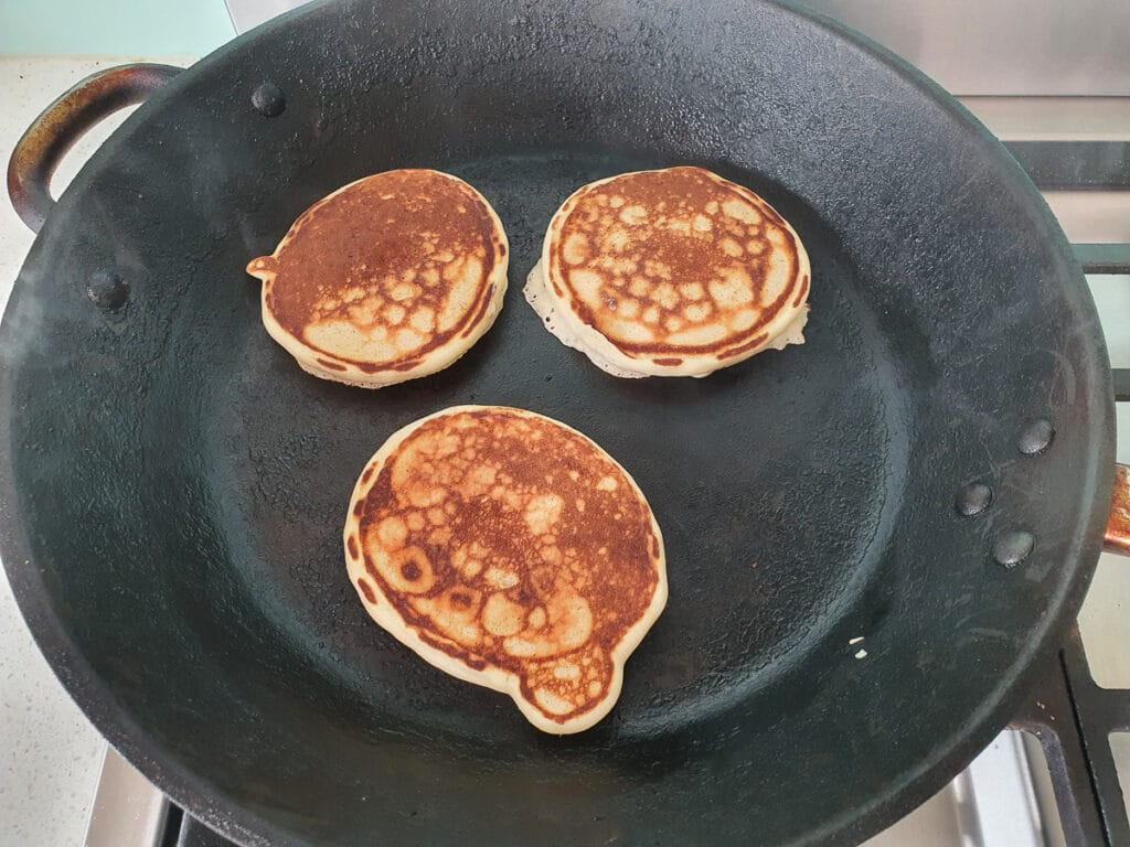 Cooking pikelets on other side in frying pan.