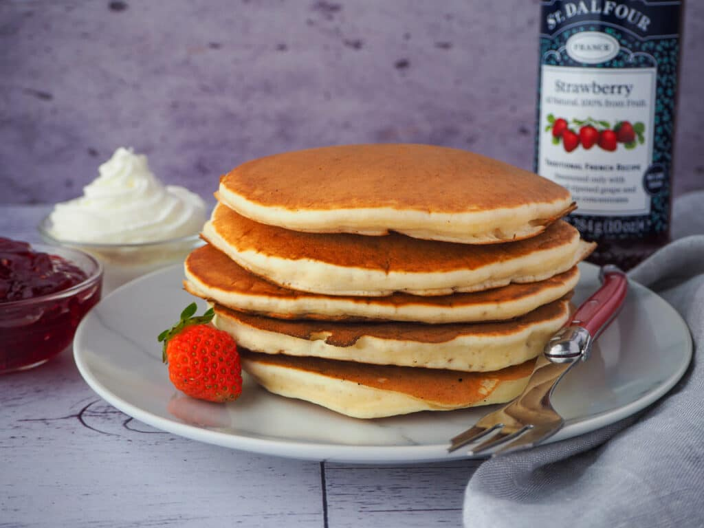 stack of pikelets on a plate, with a fresh strawberry and for, and whipped cream and jar of strawberry jam in the background,