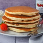 Close up stack of pikelets on a plate, with a fresh strawberry and fork, and whipped cream and jar of strawberry jam in the background,