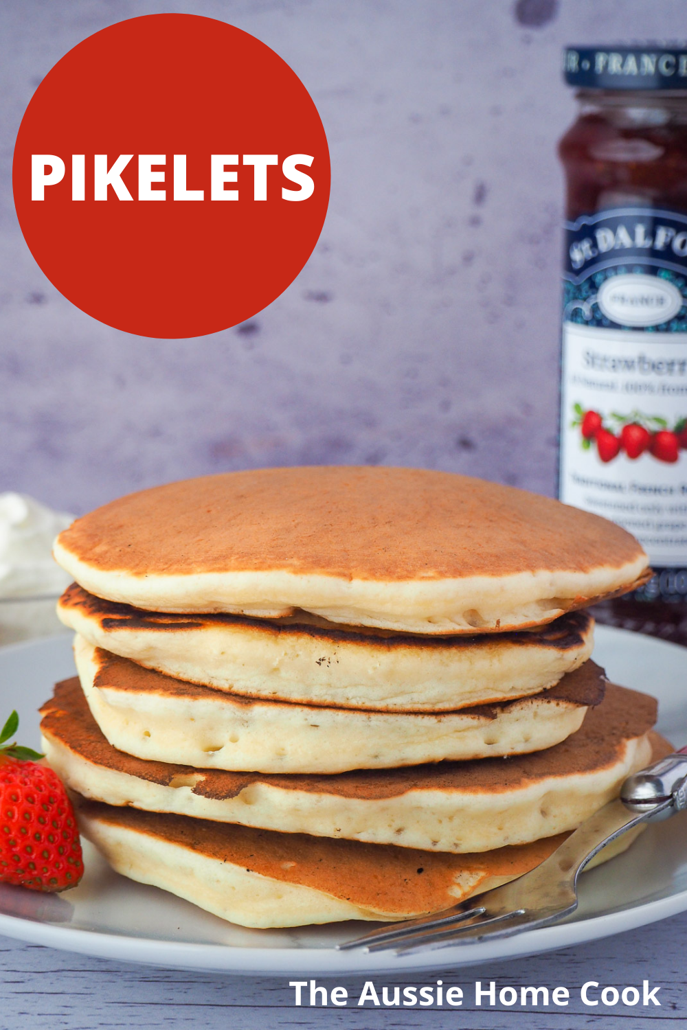 Stack of pikelets on a plate, with a fresh strawberry and fork, and whipped cream and jar of strawberry jam in the background, with text overlay Pikelets, The Aussie Home Cook.