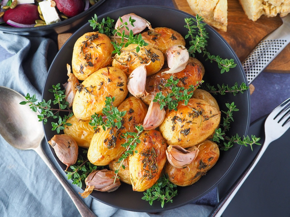 Roasted mini potatoes in a serving dish garnished with fresh herbs, silver serving spoon to the side, fresh damper, pat of butter, beetroot salad and slow cooker roast lamb on the side.