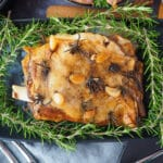 Close up slow cooker lamb roast on a serving plate, garnished with fresh rosemary.
