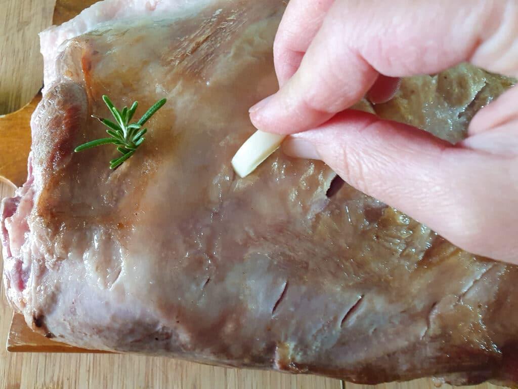 Inserting garlic sprigs into cut slits in roast.