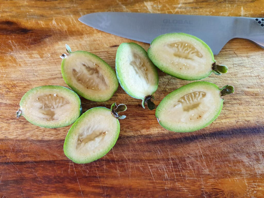 Slicing feijoas in half length ways to scoop out flesh.