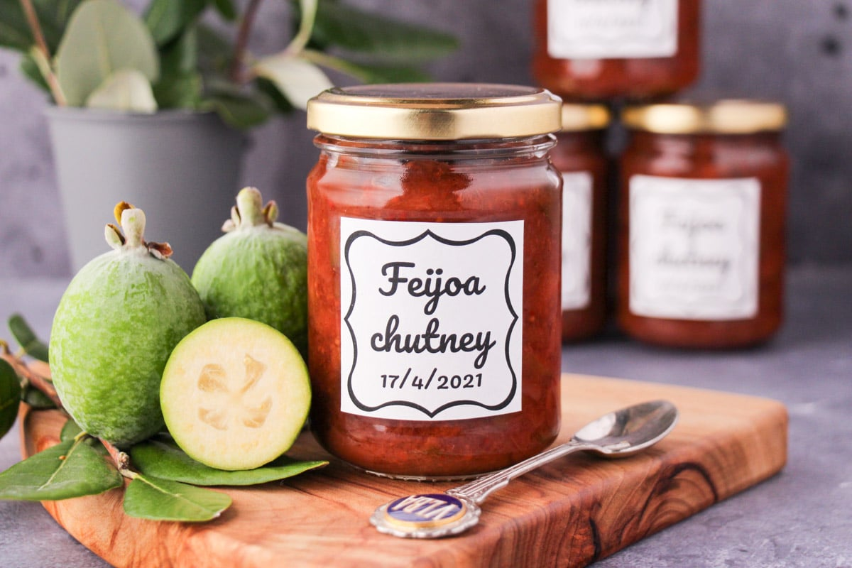 jar of homemade feijoa chutney on a board, with vintage spoon and fresh feijoas, stacked jars of chutney in the background.