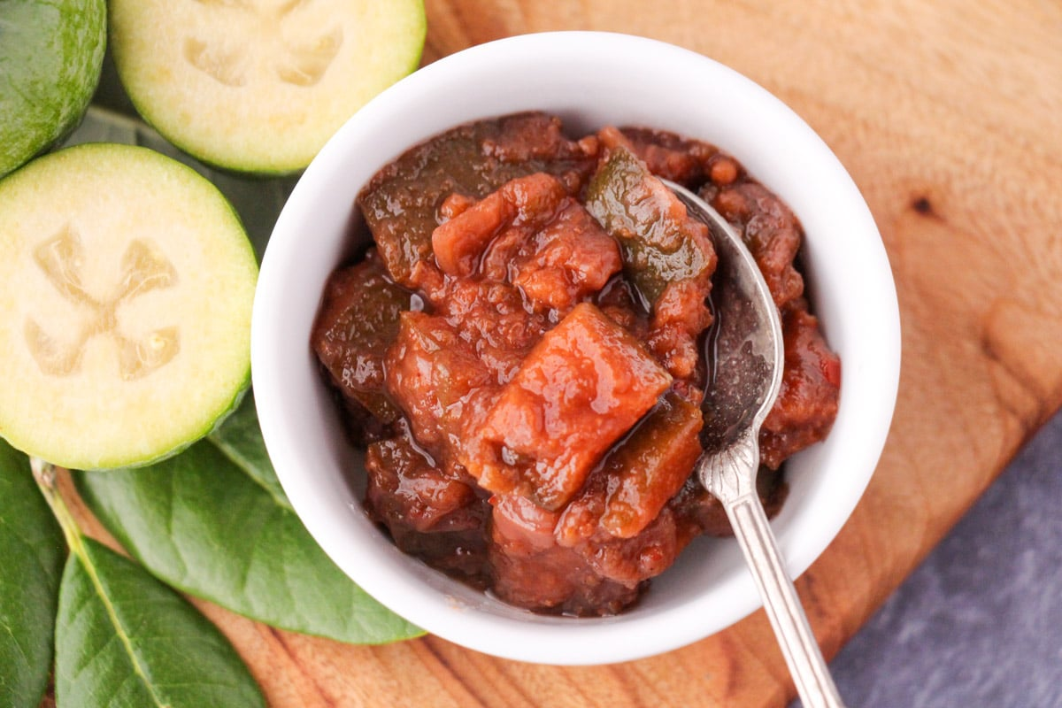 Feijoa chutney in a serving bowl on a bowl with a serving spoon, on a board with fresh feijoas and feijoa leaves.
