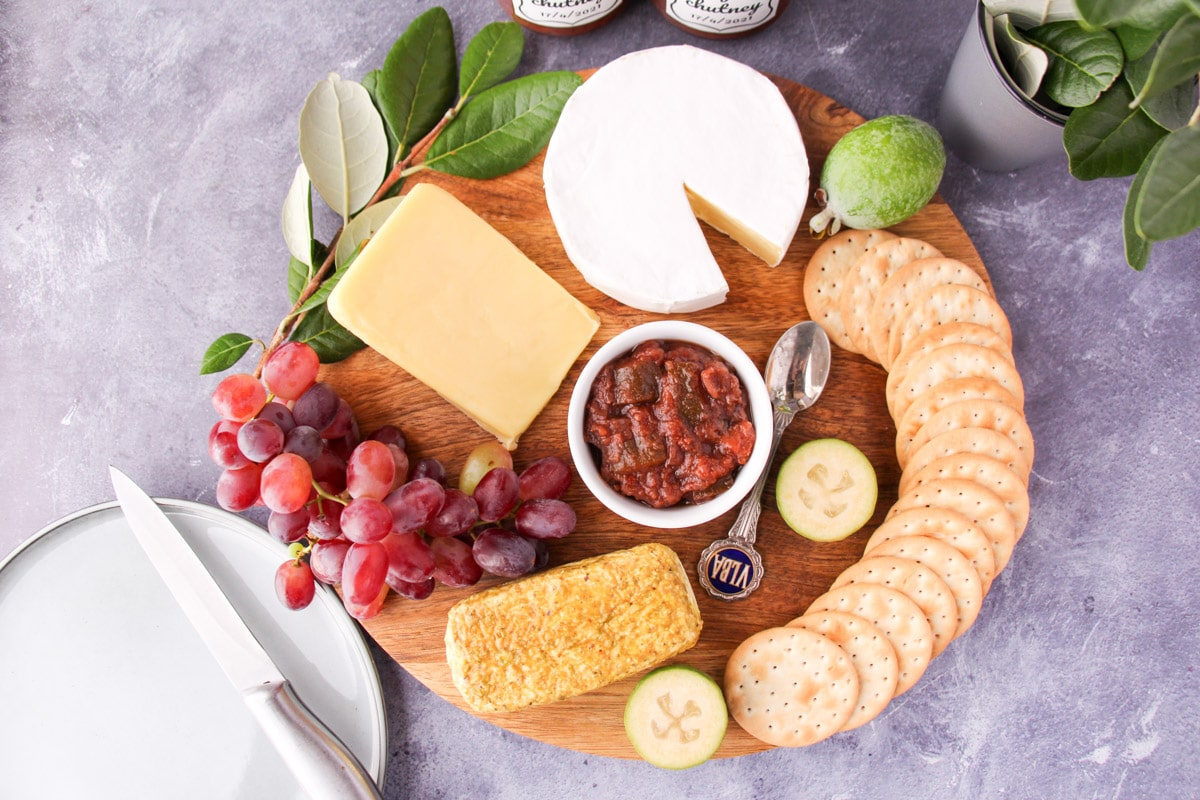 Cheeseboard with feijoa chutney, serving plate and knife, jars of chutney and fresh feijoa leaves on the side.