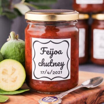 Close up jar of homemade feijoa chutney on a board, with vintage spoon and fresh feijoas, stacked jars of chutney in the background.
