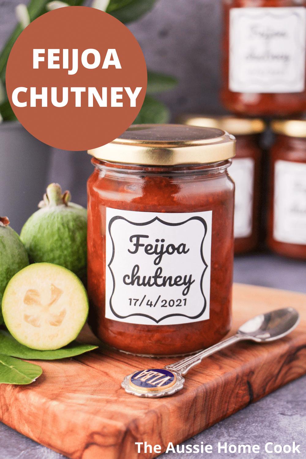 Jar of homemade feijoa chutney on a board, with vintage spoon and fresh feijoas, stacked jars of chutney in the background, and text overlay, feijoa chutney, The Aussie Home Cook.