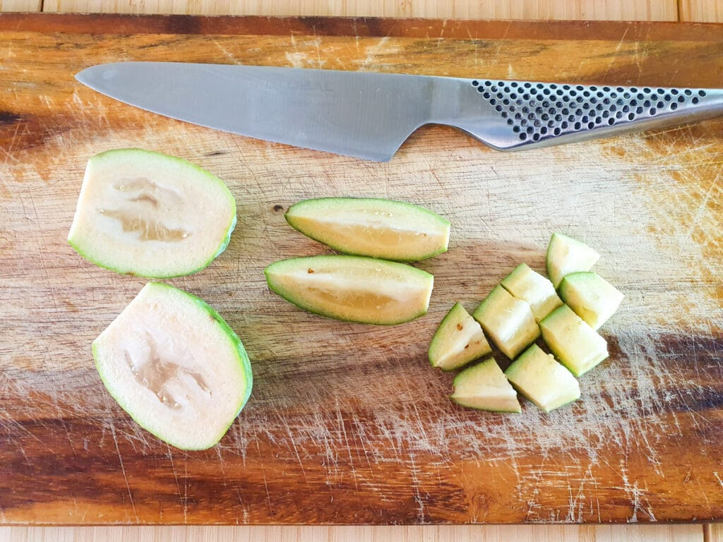 Slicing whole feijoas into bite sized pieces.