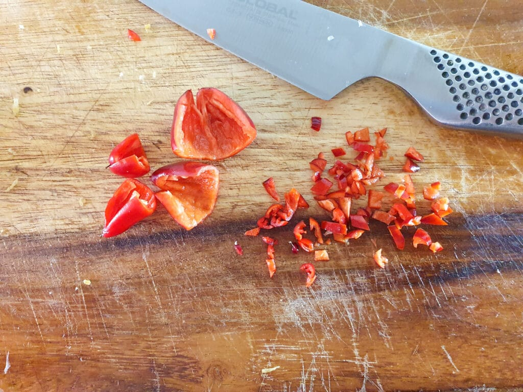 Deseeding and finely slicing chilli.