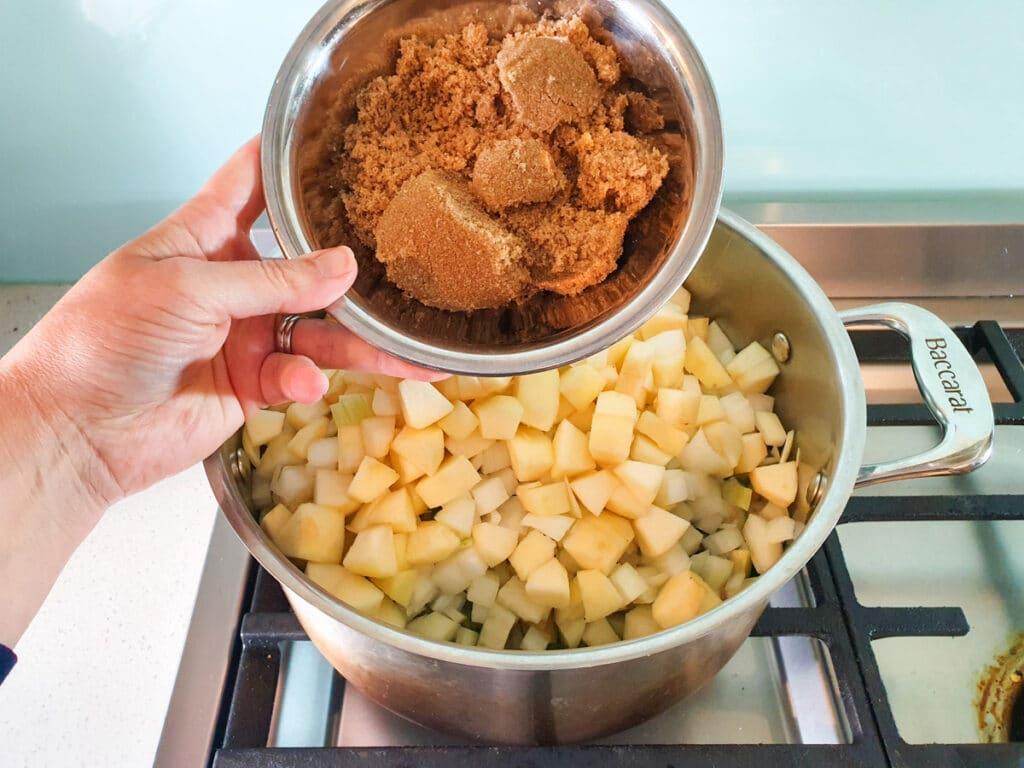 Adding brown sugar to pot.