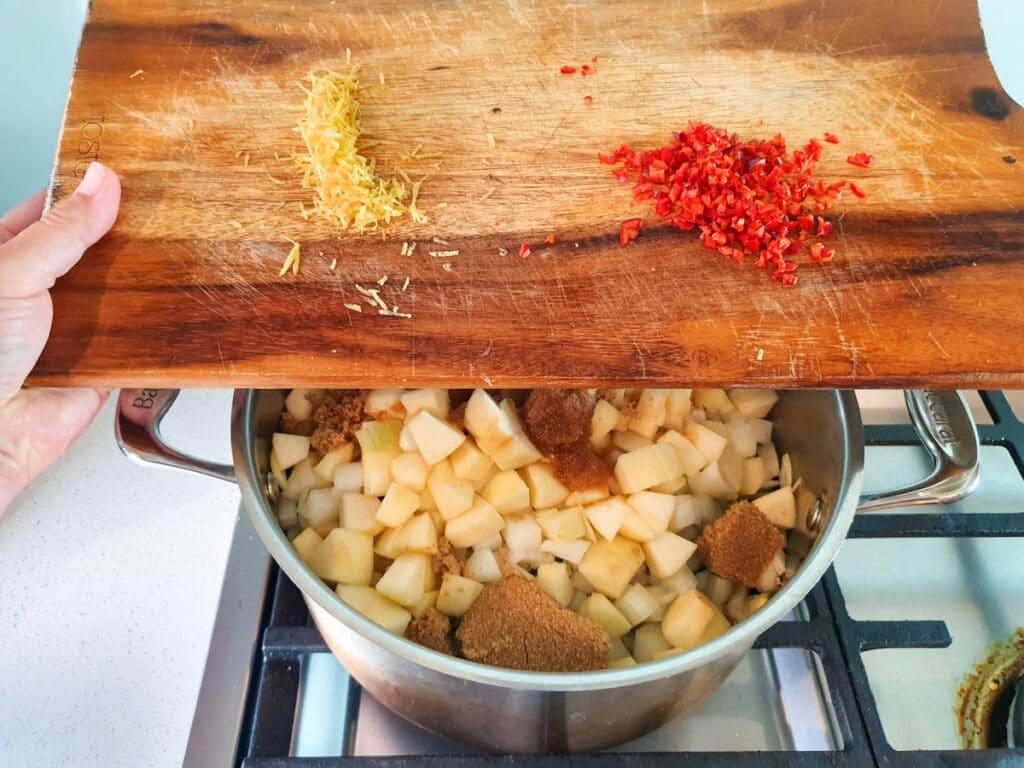 Adding lemon zest and chilli to pot.