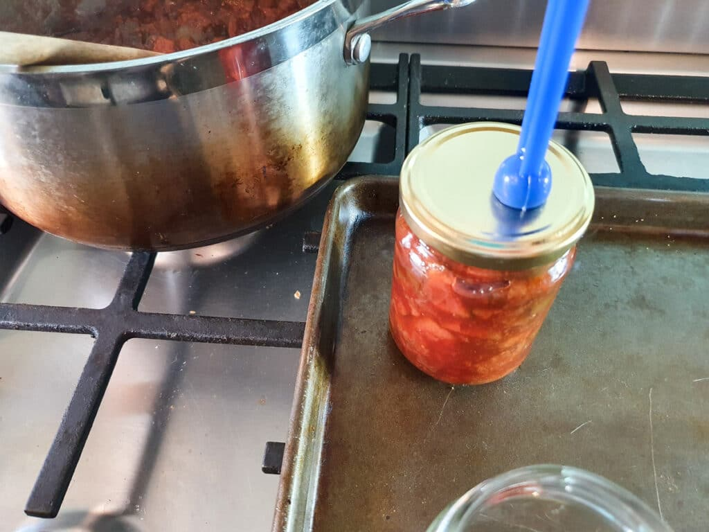 Putting sterilized lid onto filled jars.