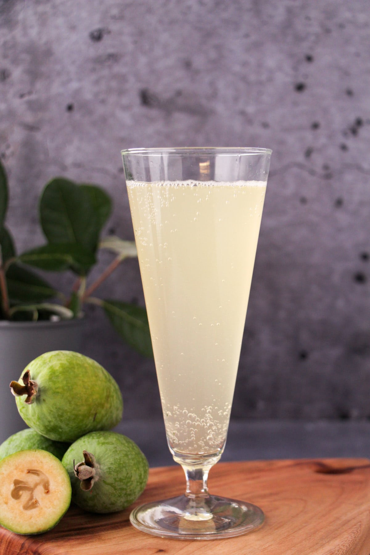 Tall glass of feijoa fizz on a board, with fresh feijoas and feijoa leaves.