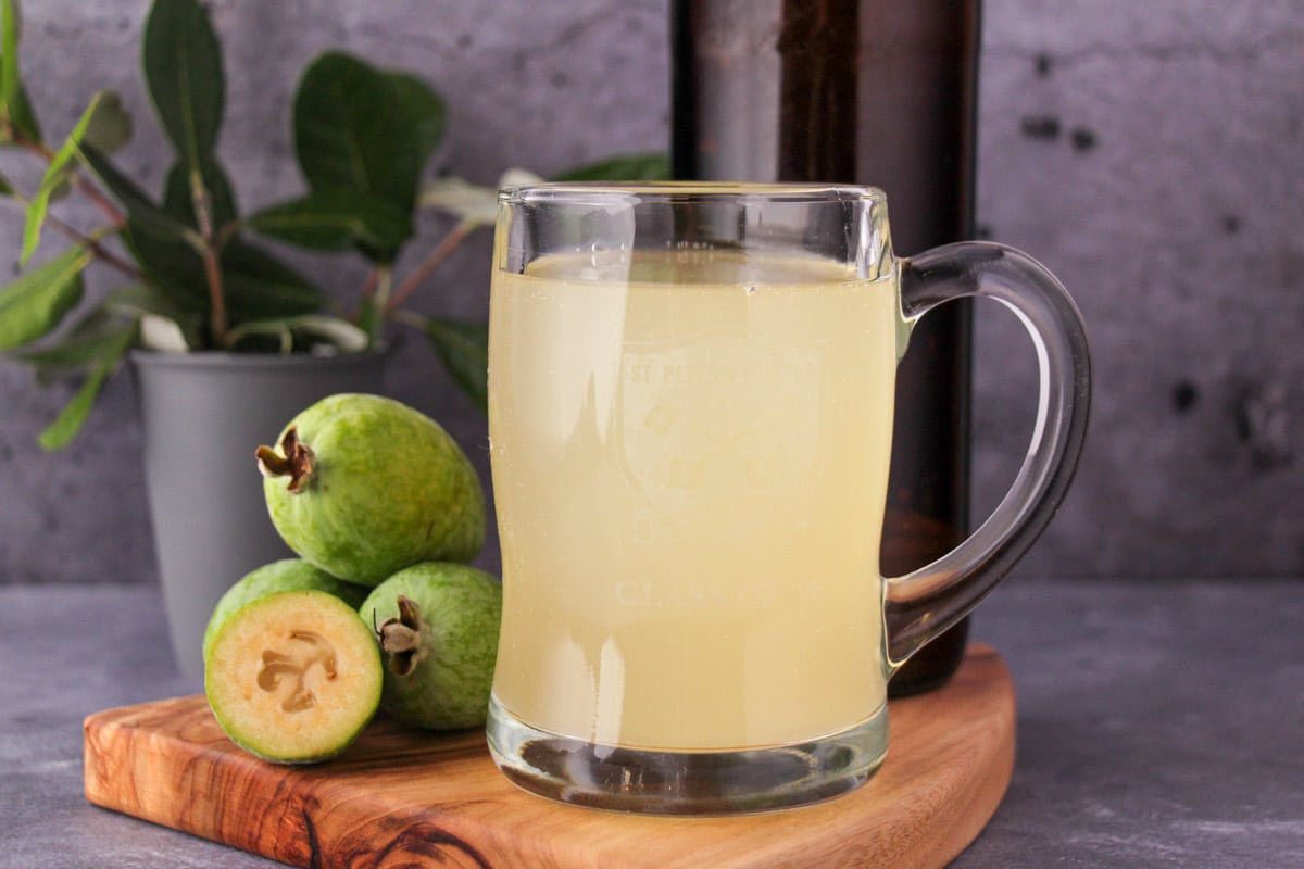 Tankard glass of feijoa fizz on a board, with bottle of feijoa fizz, fresh feijoas and feijoa leaves.