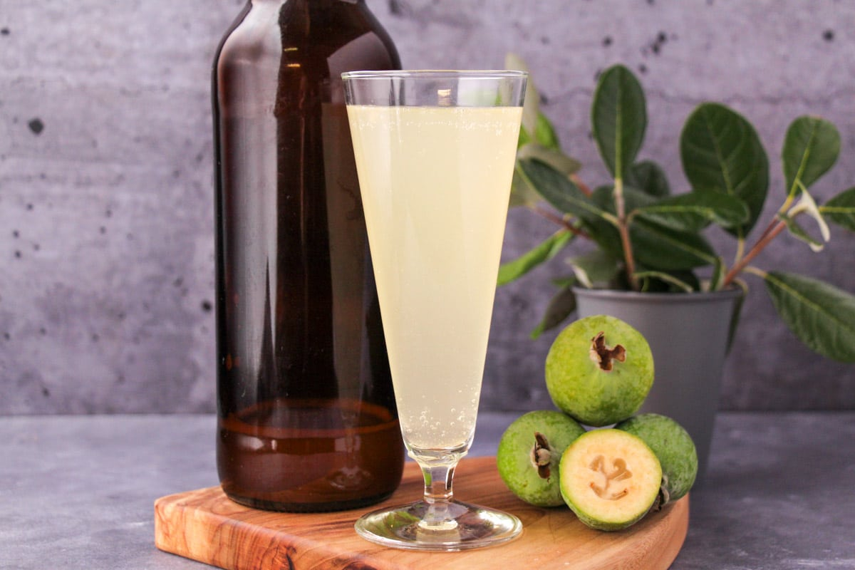 Tall glass of feijoa fizz on a board, with bottle of feijoa fizz, fresh feijoas and feijoa leaves.
