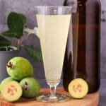 Close up tall glass of feijoa fizz on a board, with bottle of feijoa fizz, fresh feijoas and feijoa leaves.