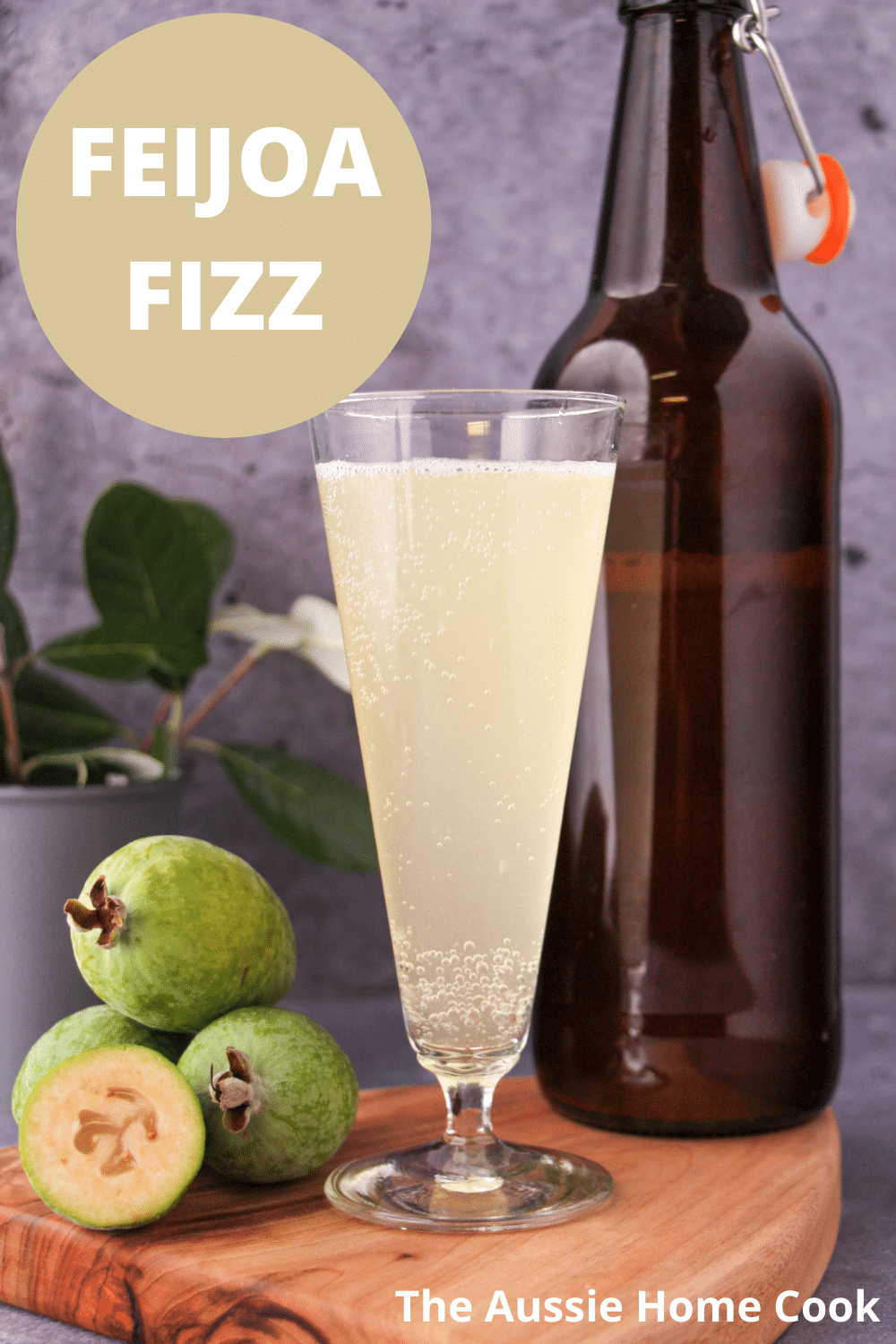 Tall glass of feijoa fizz on a board, with bottle of feijoa fizz, fresh feijoas and feijoa leaves, with text overlay, feijoa fizz and The Aussie Home Cook.