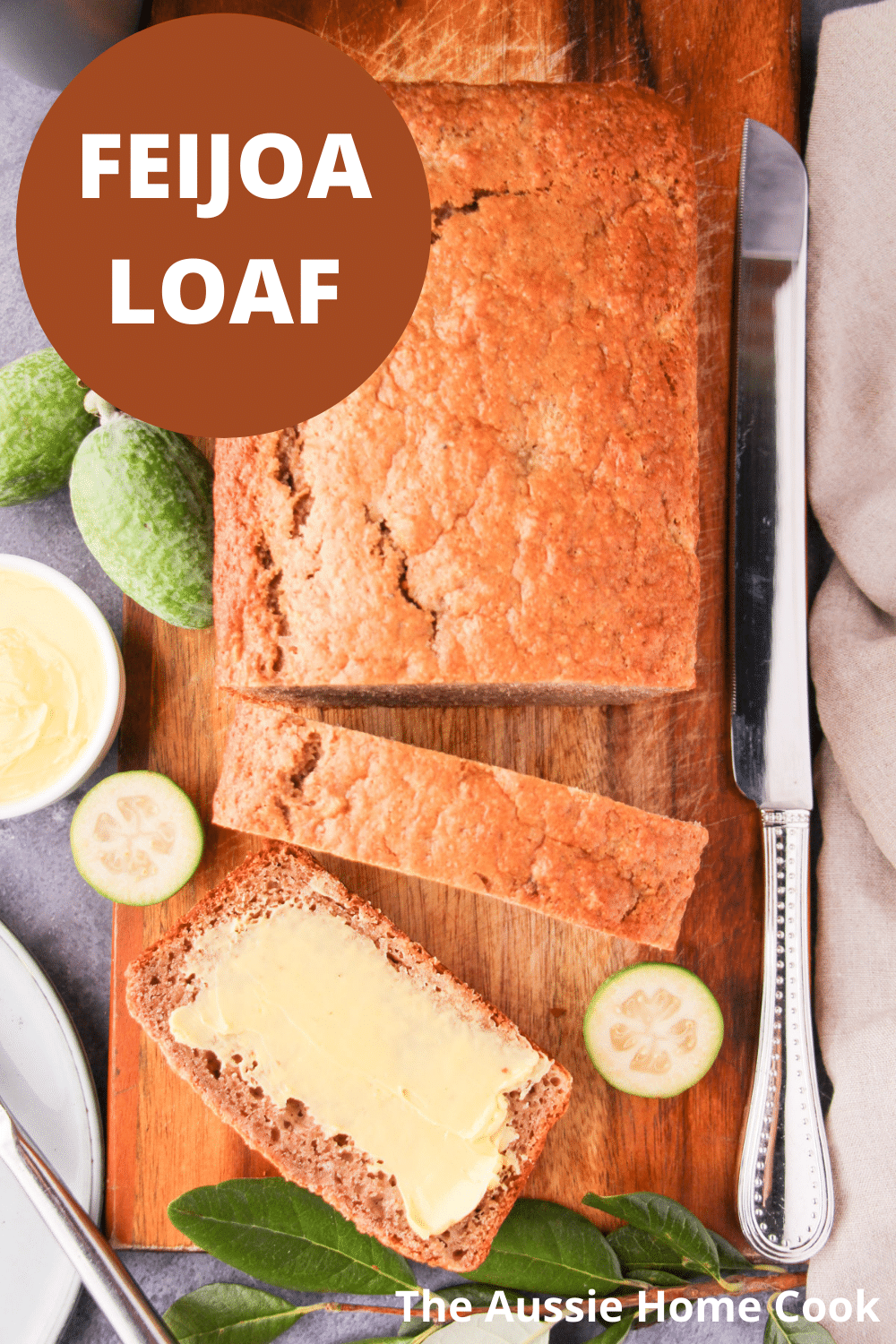 Sliced feijoa loaf on a chopping board, with one buttered slice, fresh feijoas and leaves, large cutting knife, butter and plate and knife on the side, with text overlay, feijoa loaf and The Aussie Home Cook.
