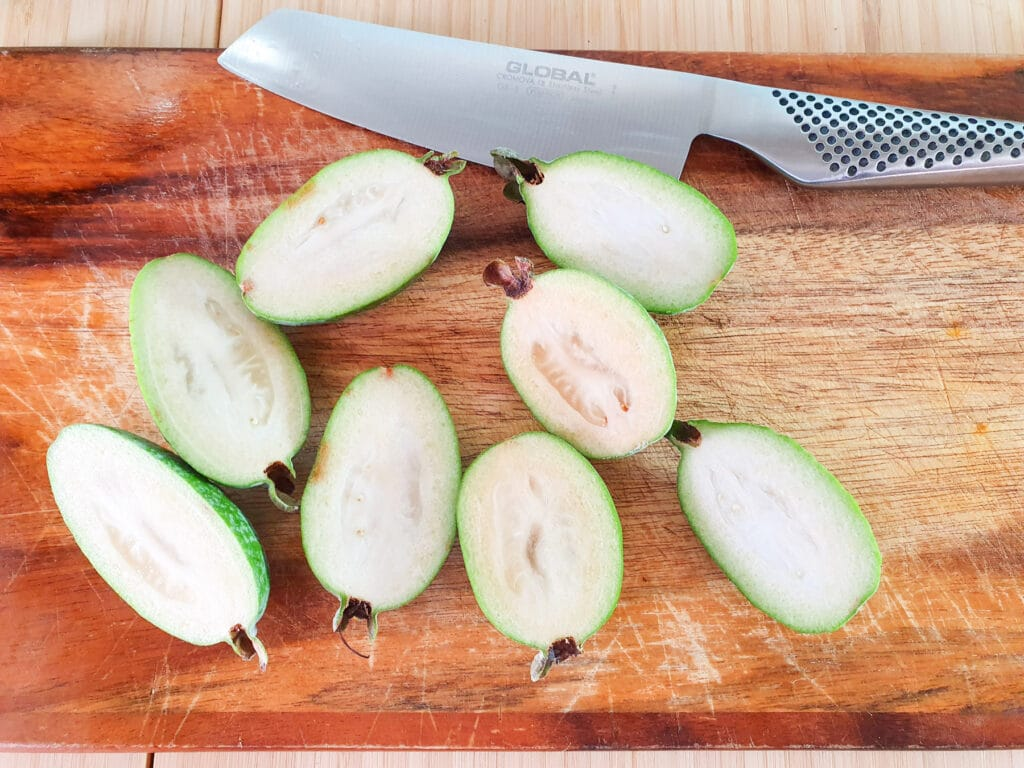 Slicing open feijoas length ways to scoop out flesh.